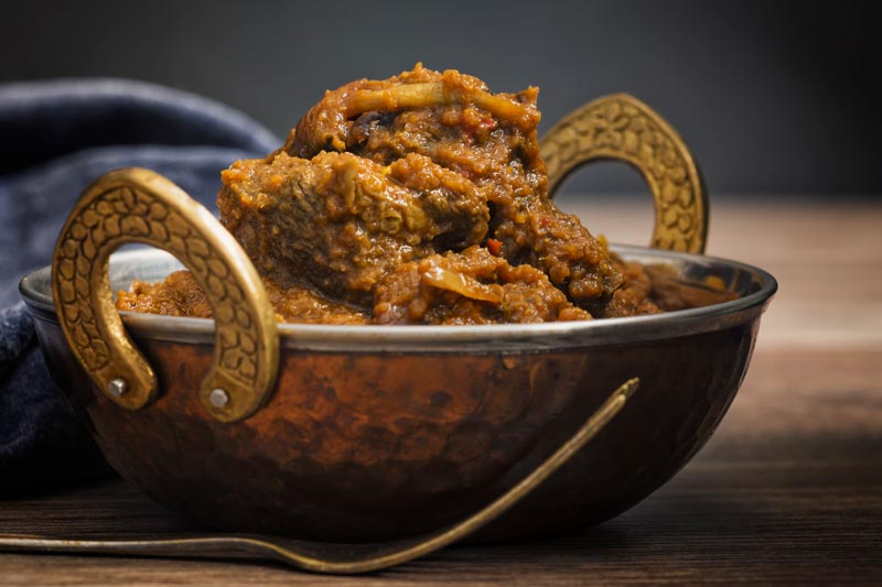 Landscape image of a beef dopiaza curry served in a hammered copper coloured curry bowl