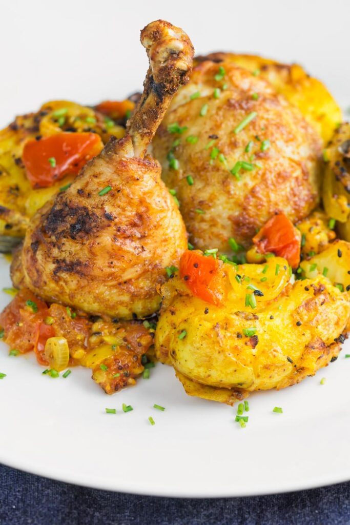 Portrait close up image of lightly crushed Bombay potatoes on a white plate with roast chicken legs and snipped chives