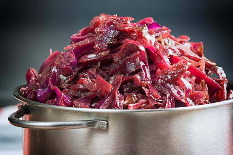 Landscape close up image of braised red cabbage served in a small aluminium pan