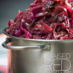 Portrait close up image of braised red cabbage served in a small aluminium pan with text overlay