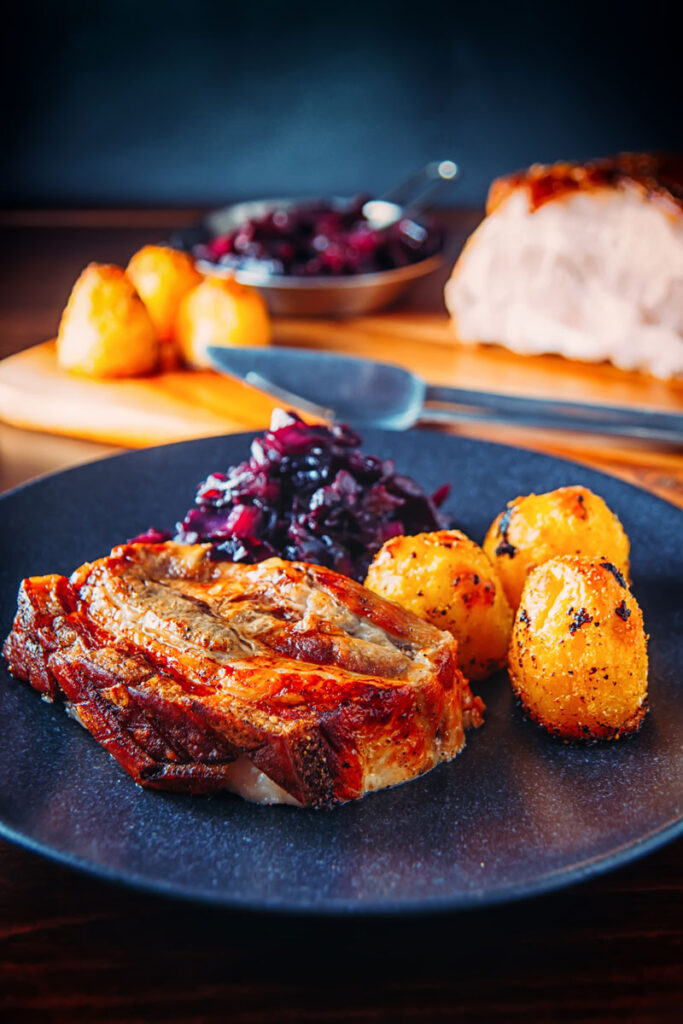 Portrait image of a classic Sunday lunch featuring roast pork, roast potatoes and braised red cabbage