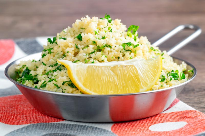 Landscape image of a herby buttered couscous served with a lemon wedge
