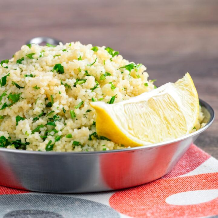 Square image of a herby buttered couscous served with a lemon wedge