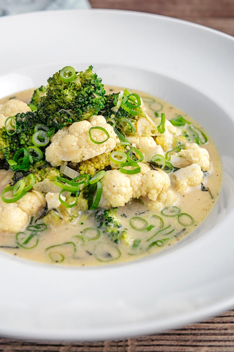 Portrait image of a green Thai curry soup with cauliflower and broccoli served in a white bowl