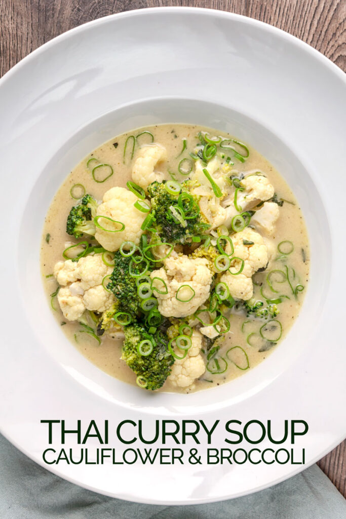 Portrait overhead image of a green Thai curry soup with cauliflower and broccoli served in a white bowl with text overlay