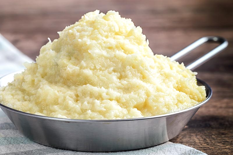 Landscape image of celeriac mash served in a pan on a rustic wooden table