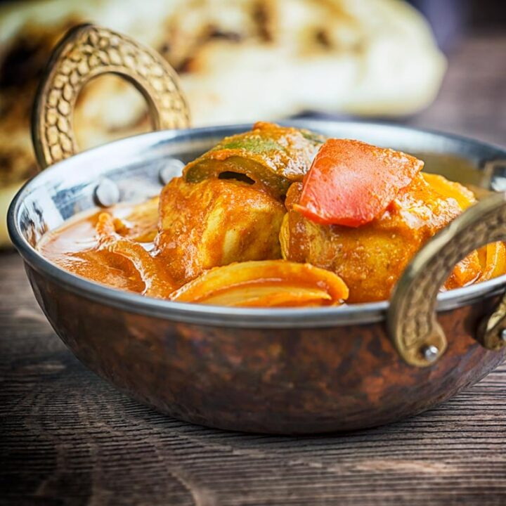 Square image of a chicken balti curry in a copper coloured curry bowl served with a naan bread