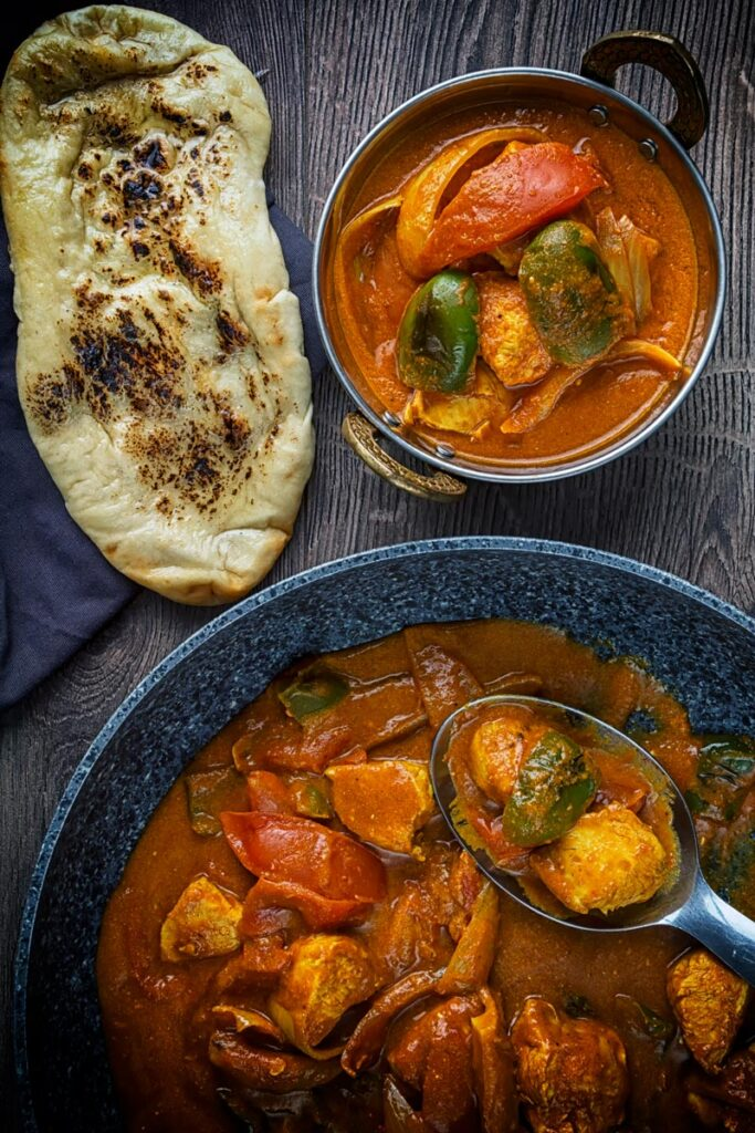 Portrait overhead image of a chicken balti curry in a copper coloured curry bowl served with a naan bread