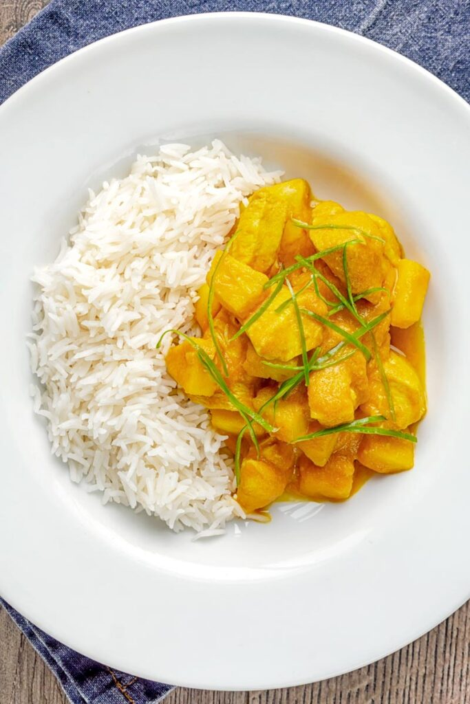Portrait overhead image of a chicken and pineapple curry in a thick sauce with a chiffonade of green chilli and white rice served in a white bowl