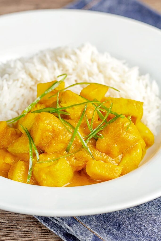 Portrait image of a chicken and pineapple curry in a thick sauce with a chiffonade of green chilli and white rice served in a white bowl