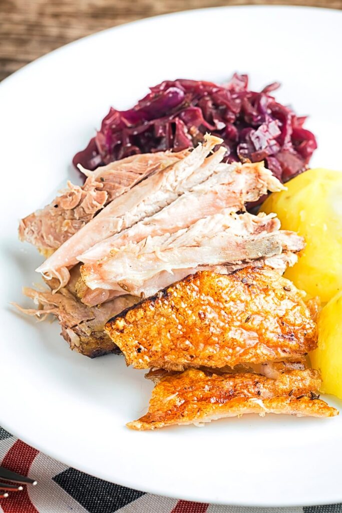 Portrait image of the meat from a roast pork knuckle served on a white plate with crispy crackling, red cabbage and boiled potatoes.