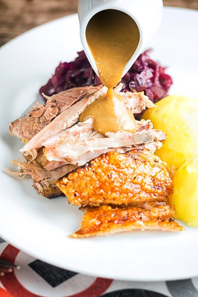 Portrait image of the meat from a roast pork knuckle having gravy poured over it served on a white plate with crispy crackling, red cabbage and boiled potatoes.