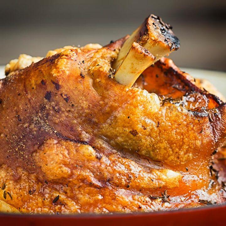 Square close up image of a roasted crispy pork knuckle showing crisp crackling