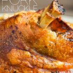 Portrait close up of a roasted crispy pork knuckle showing crisp crackling with text overlay