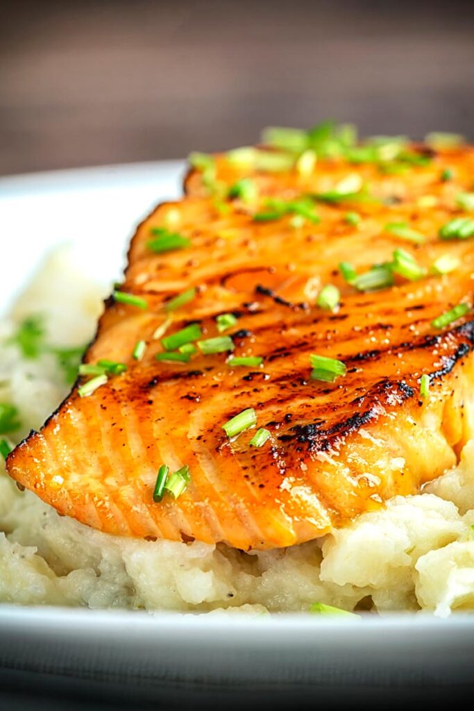 Portrait close up image of honey and soy glazed salmon fillet served on a pile of celeriac mash on a white plate