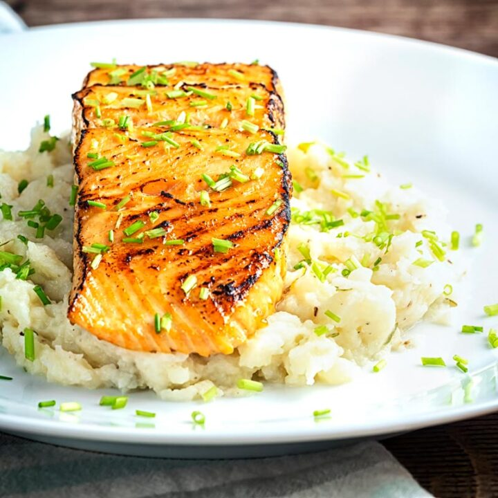 Square image of honey and soy glazed salmon fillet served on a pile of celeriac mash on a white plate