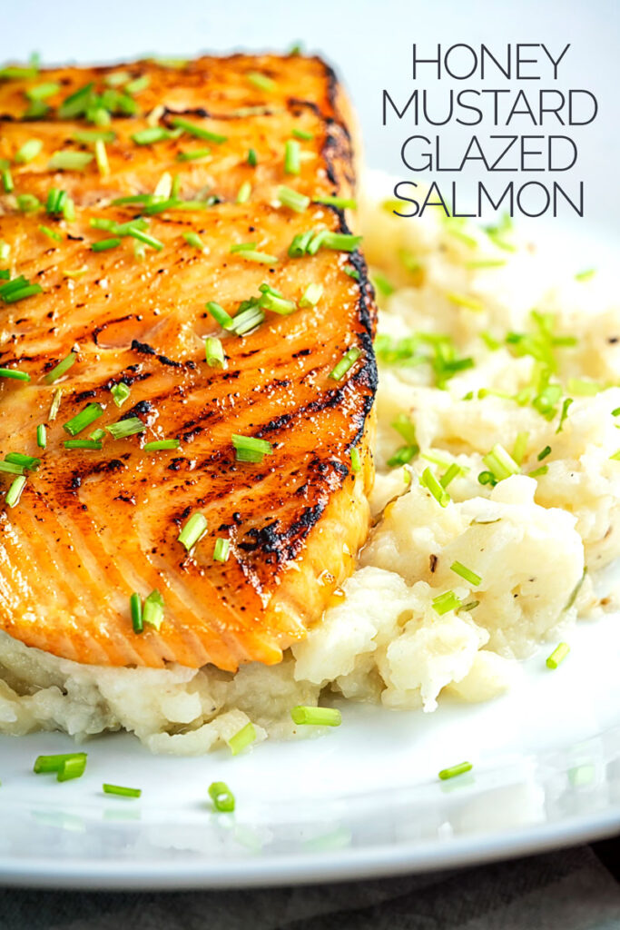 Portrait profile image of honey and soy glazed salmon fillet served on a pile of celeriac mash on a white plate with text overlay