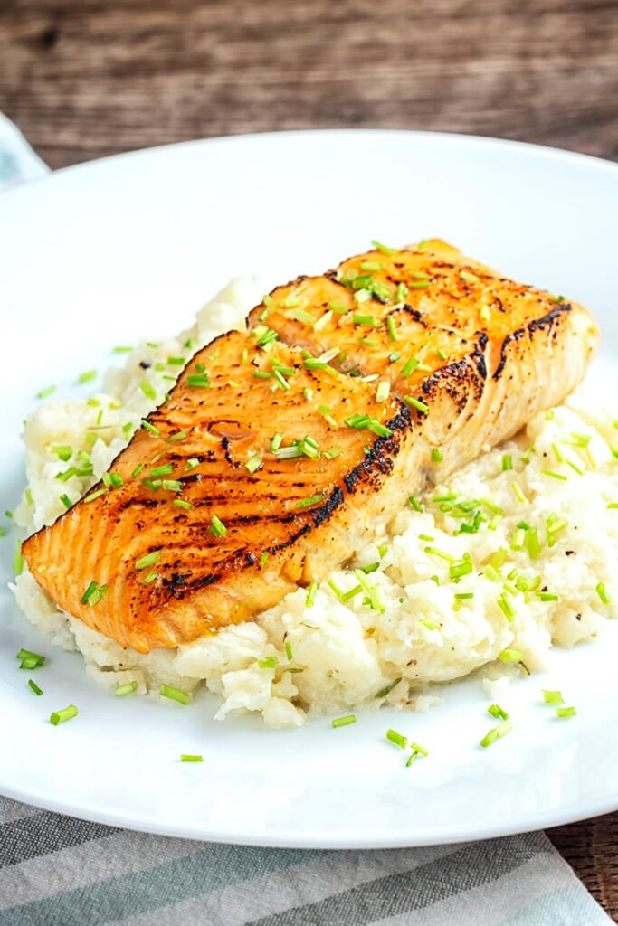 Portrait image of honey and soy glazed salmon fillet served on a pile of celeriac mash on a white plate
