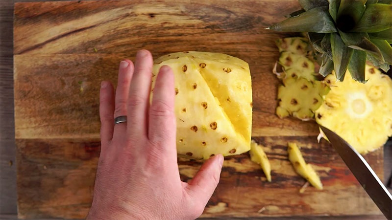 Step 5 in how to prepare a pineapple, remove eyes with second side of v shaped cut