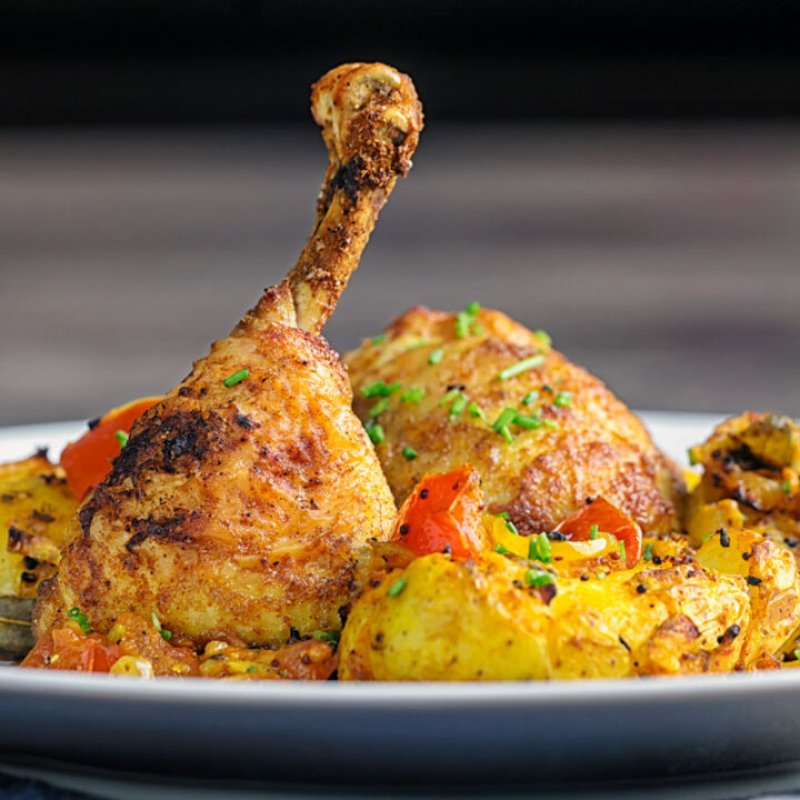 Square image of Indian spiced roast chicken legs served with Bombay potatoes on a white plate