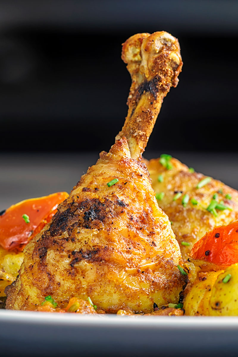 Portrait image of Indian spiced roast chicken legs served with Bombay potatoes on a white plate