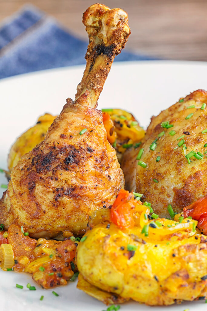 Portrait image of Indian spiced roast chicken legs served with Bombay potatoes on a white plate close up