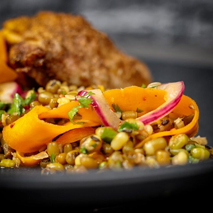 Square image of a carrot and mung bean salad with pickled carrot ribbons and red onions on a black plate