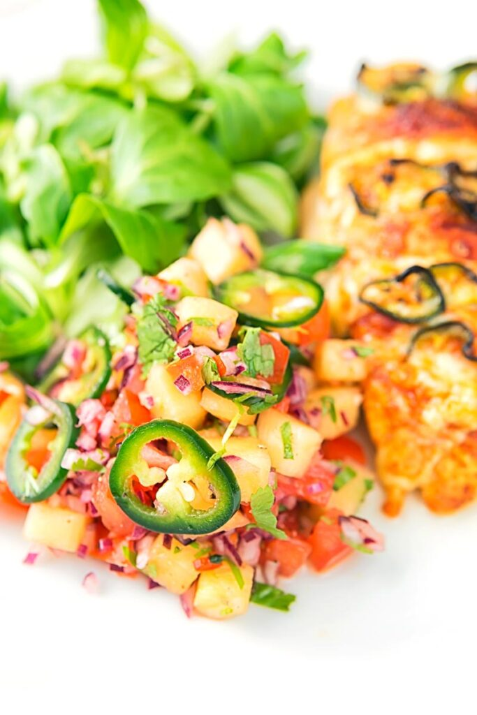 Portrait image of a pineapple salsa served as a side to a chicken breast with green salad