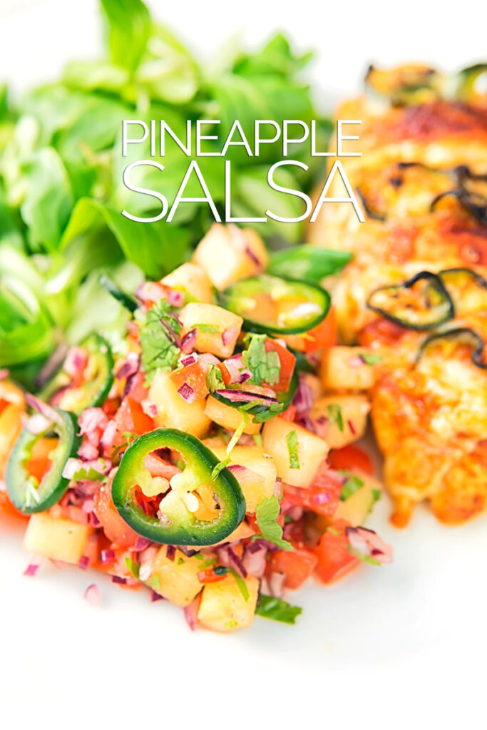 Portrait image of a pineapple salsa served as a side to a chicken breast with green salad with text overlay