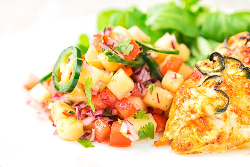 Landscape image of a pineapple salsa served as a side to a chicken breast with green salad