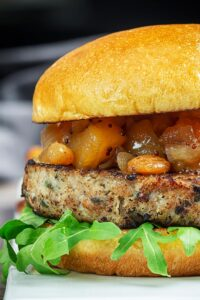 Portrait close up profile image of a pork and apple burger served on a white rectangle plate with a chutney topping