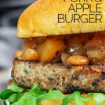 Portrait close up profile image of a pork and apple burger served on a white rectangle plate with a chutney topping with text overlay