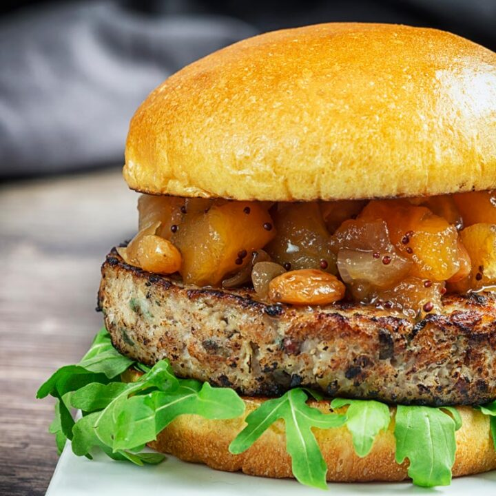 Square image of a pork and apple burger served on a white plate with a chutney topping