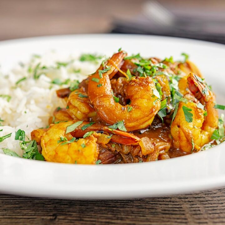 Square image of an Indian prawn curry served with white rice and garnished with coriander