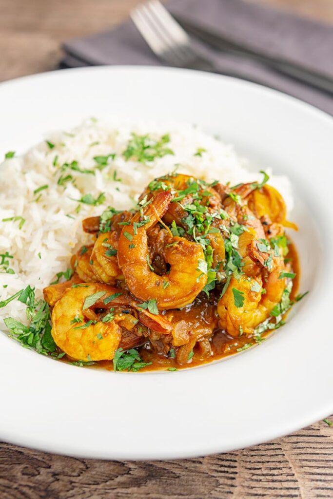 Portrait image of an Indian prawn curry served with white rice and garnished with coriander