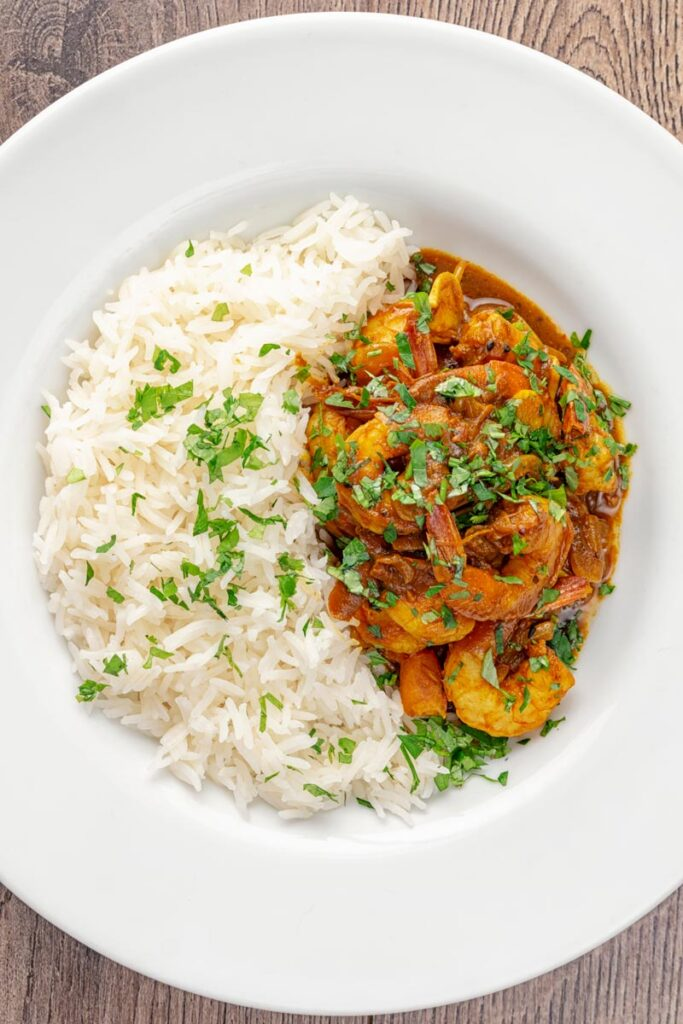 Portrait overhead image of an Indian prawn curry served with white rise and garnished with coriander