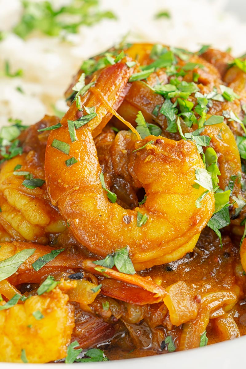 Portrait close up image of an Indian prawn curry served with white rise and garnished with coriander