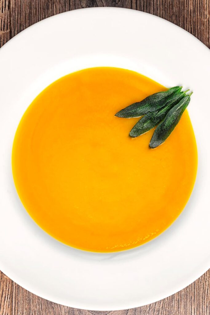 Portrait overhead image of a bowl of silky roast butternut squash soup served with fried sage leaves