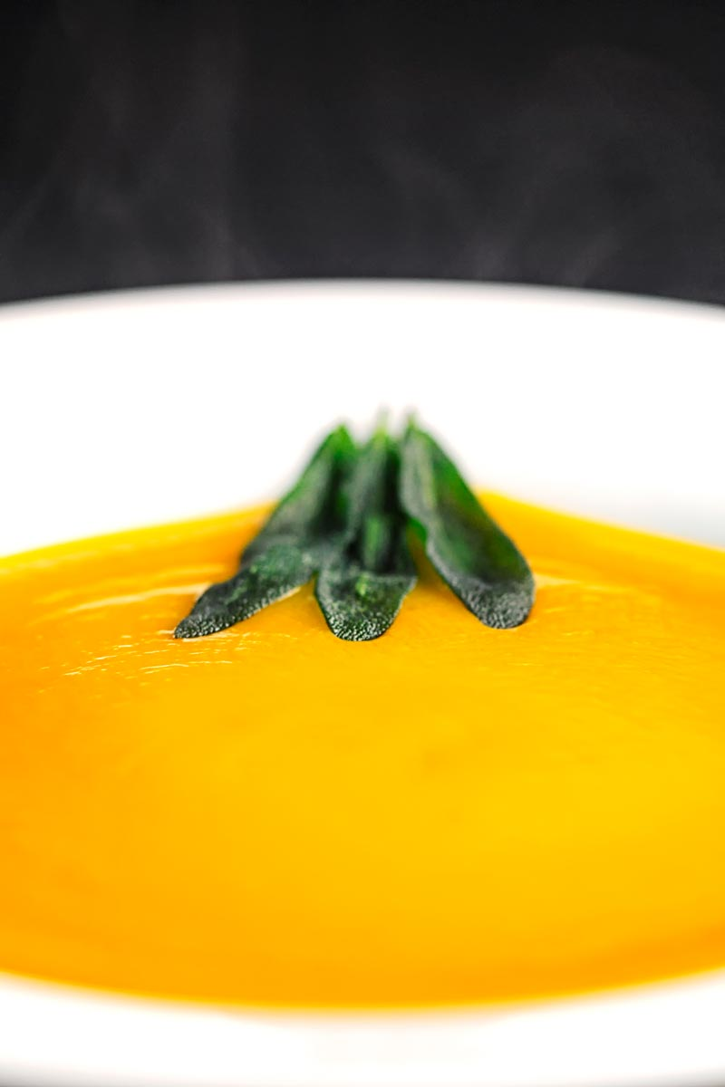 Portrait close image of a bowl of silky steaming hot roasted butternut squash soup served with fried sage leaves