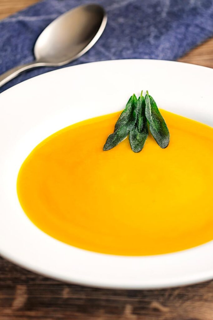 Portrait image of a bowl of silky roast butternut squash soup served with fried sage leaves