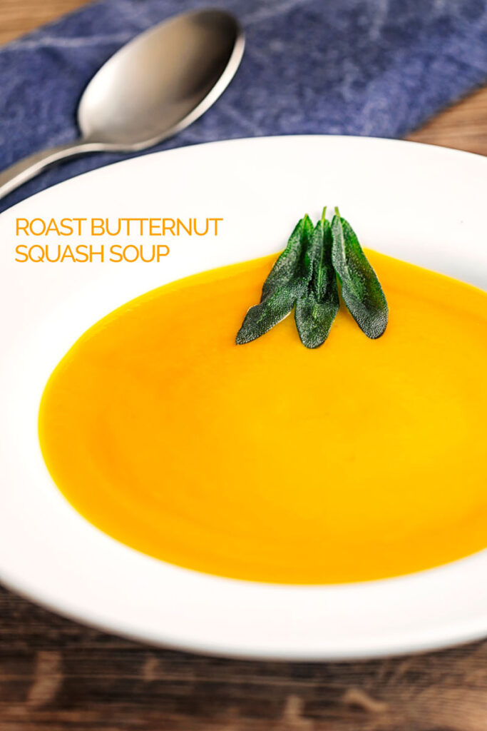 Portrait image of a bowl of silky roast butternut squash soup served with fried sage leaves with text overlay
