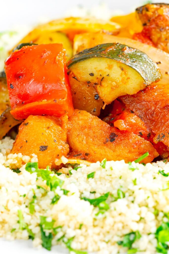 Portrait close up image of a vegetable tagine served on a white plate with herby buttered couscous