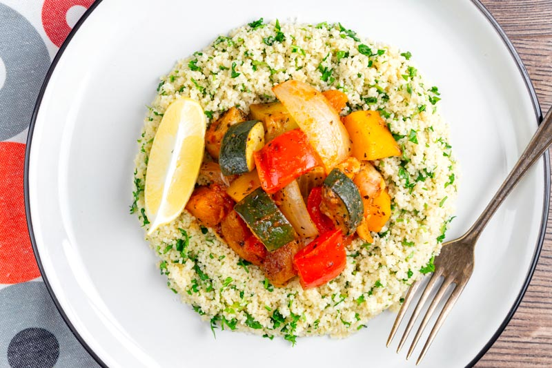 Landscape overhead image of a vegetable tagine served on a white plate with herby buttered couscous