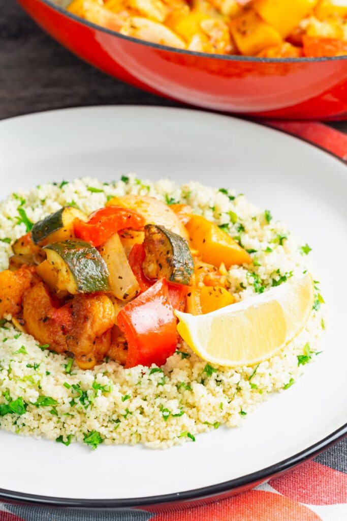 Portrait image of a vegetable tagine served on a white plate with herby buttered couscous