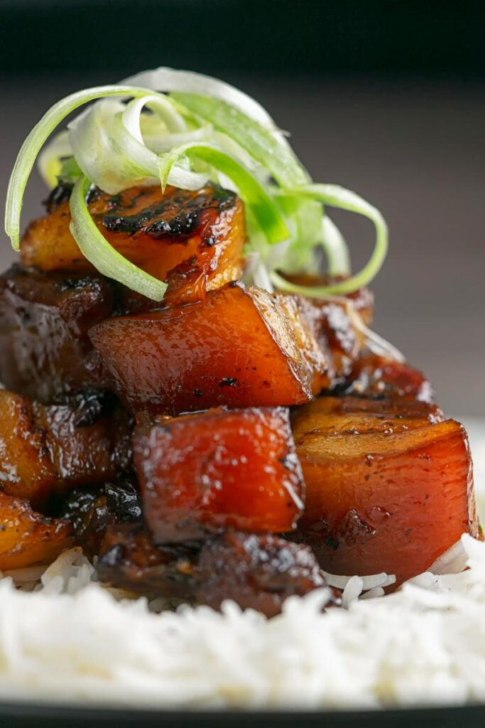 Portrait close up image of a single serving of glazed sticky pork belly with pineapple on a bed of rice and garnish of shredded green onion