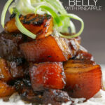 Portrait close up image of a single serving of glazed sticky pork belly with pineapple on a bed of rice and garnish of shredded green onion with a text overlay