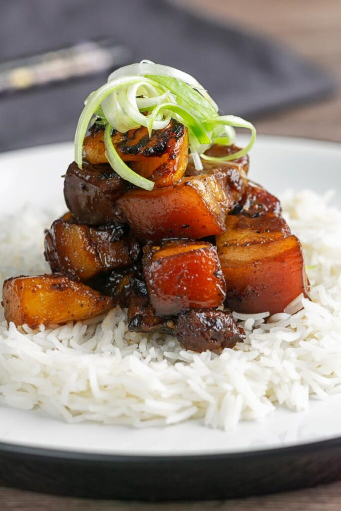 Portrait image of a single serving of glazed sticky pork belly with pineapple on a bed of rice and garnish of shredded green onion on a white plate