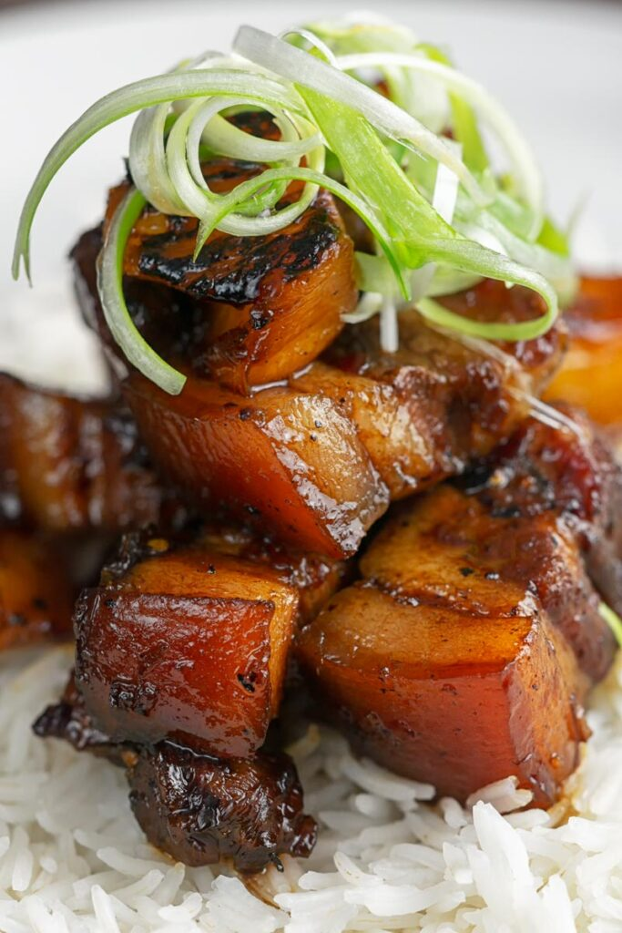 Portrait image of a single serving of glazed sticky pork belly with pineapple on a bed of rice and garnish of shredded green onion