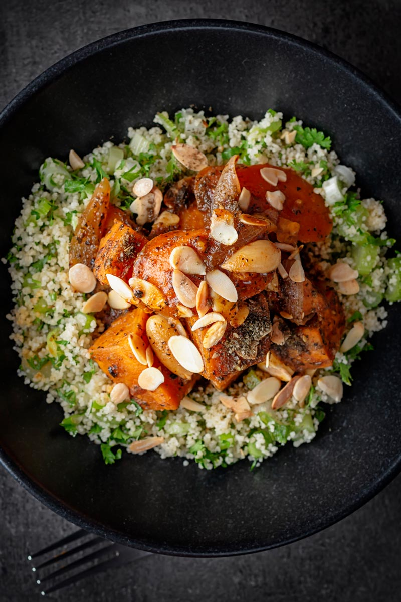 Portrait overhead image of a vegetarian sweet potato tagine garnished with flaked almonds and zaatar on a bed of couscous