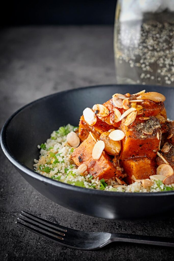Portrait image of a vegetarian sweet potato tagine garnished with flaked almonds and zaatar on a bed of couscous